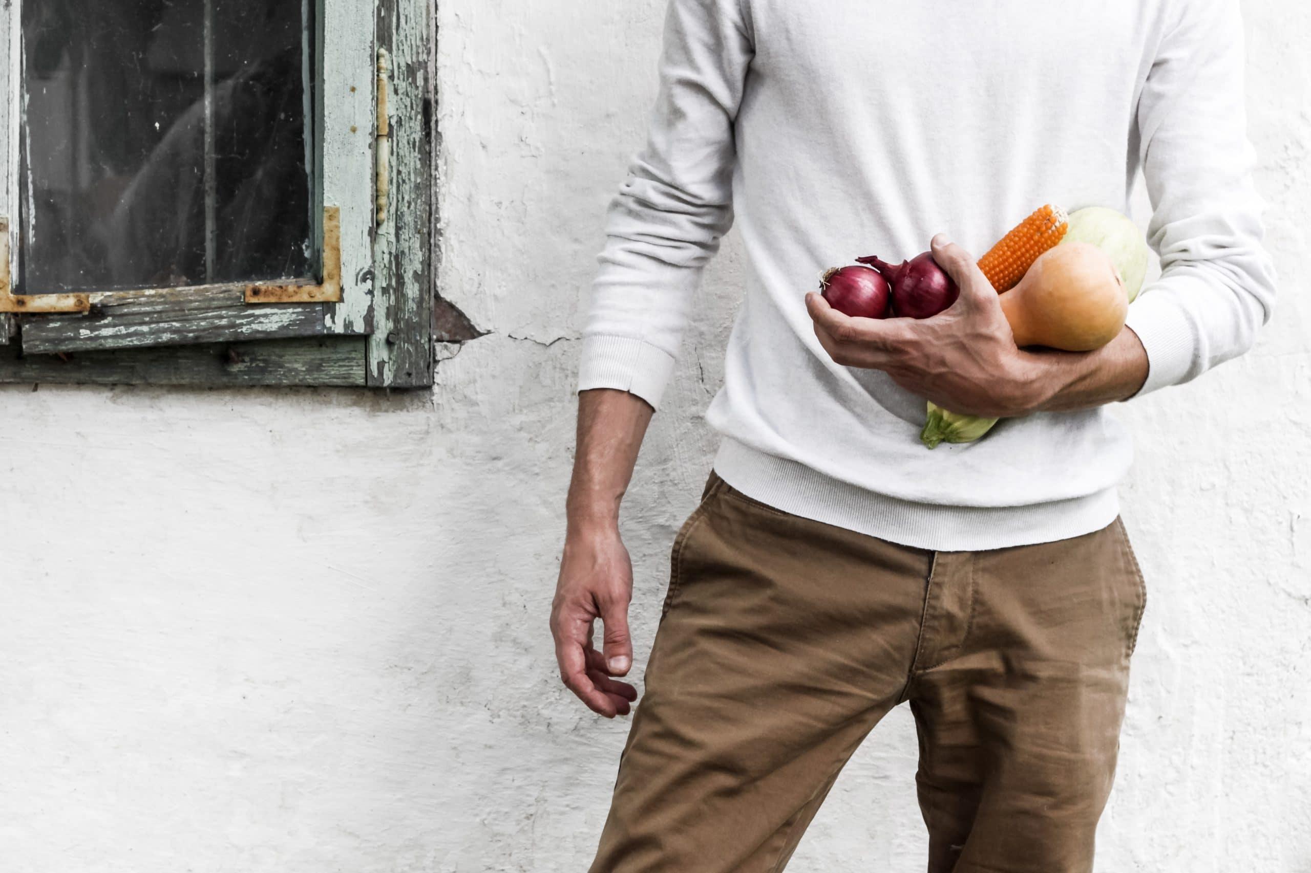Vegetais nas mãos de um homem.