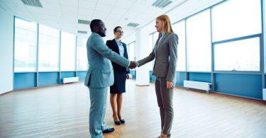 Homem negro apertando a mão de uma mulher branca e loira, ambos ao lado de uma mulher branca com cabelos castanhos. Todos usam roupas sociais e estão dentro de um escritório.