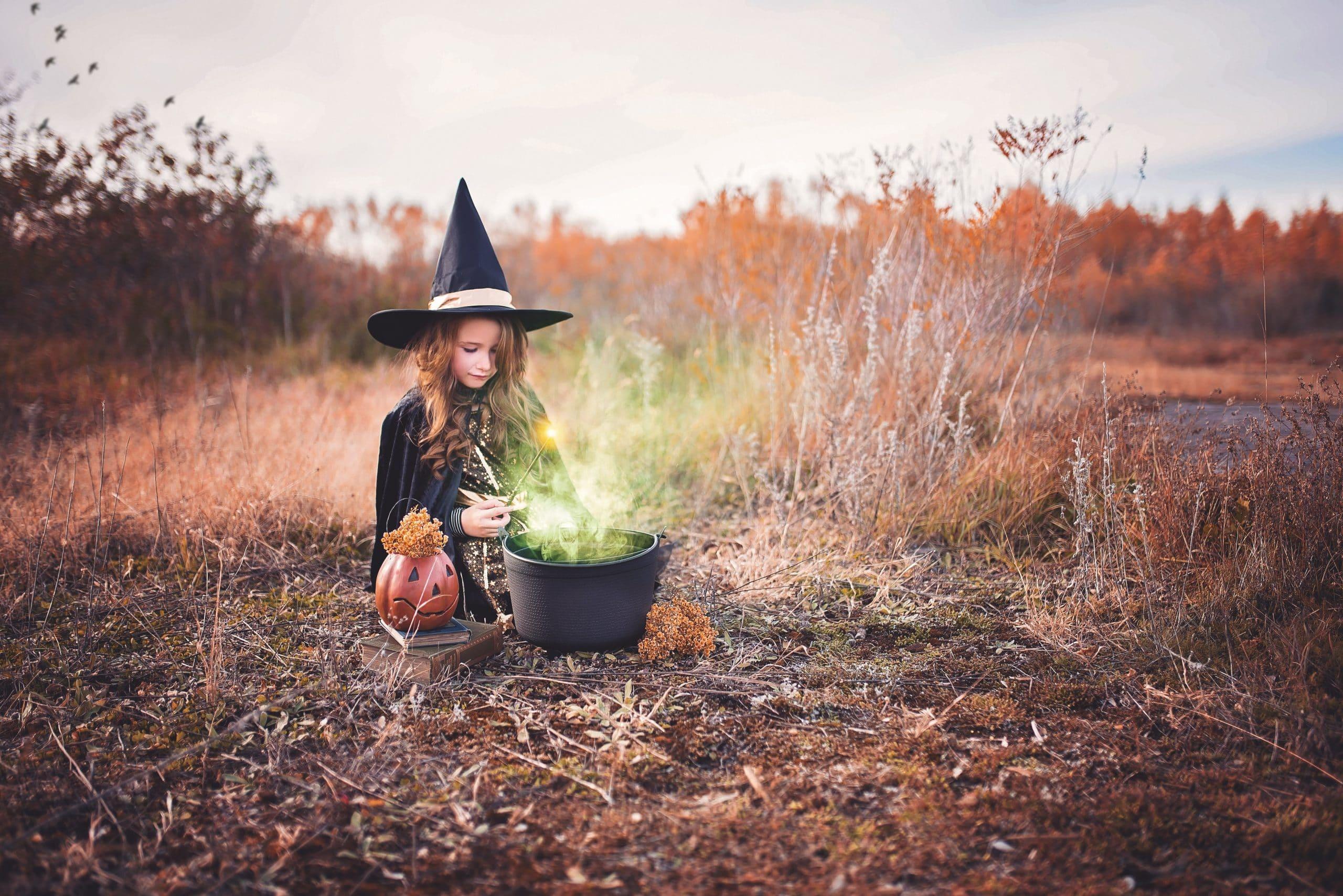 Criança vestida de bruxa com caldeirão saindo fumaça