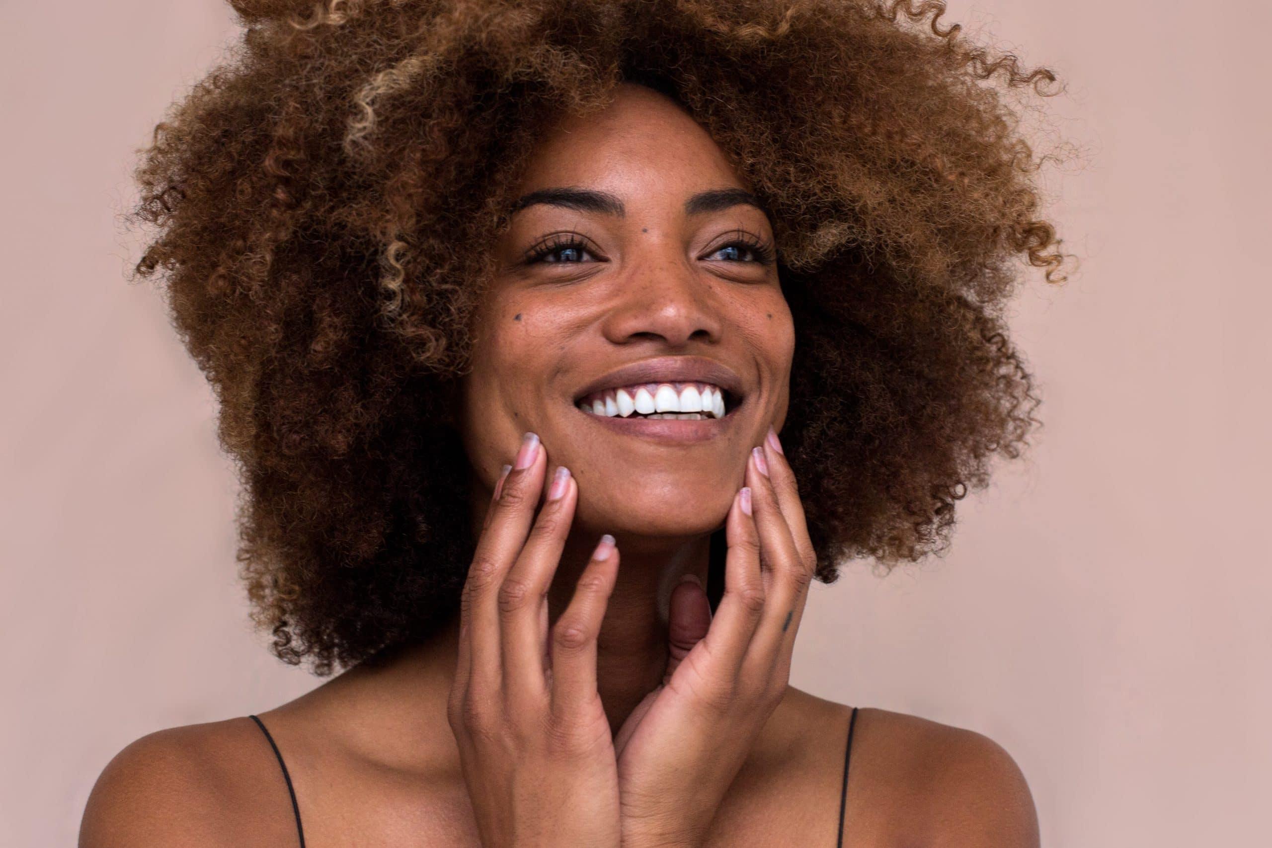 Mulher sorrindo com as mãos nas bochechas.