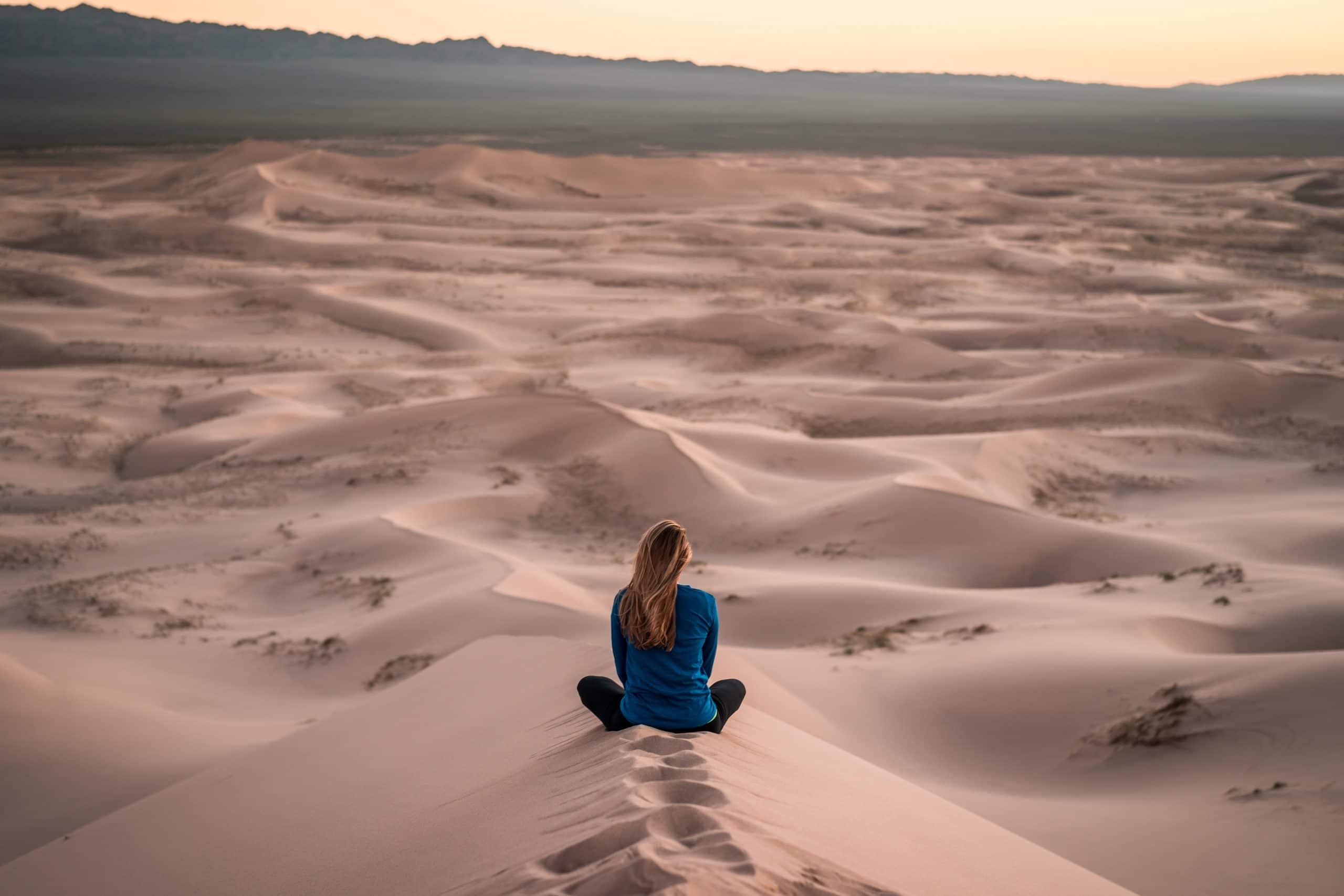 Mulher sentada em deserto de areia