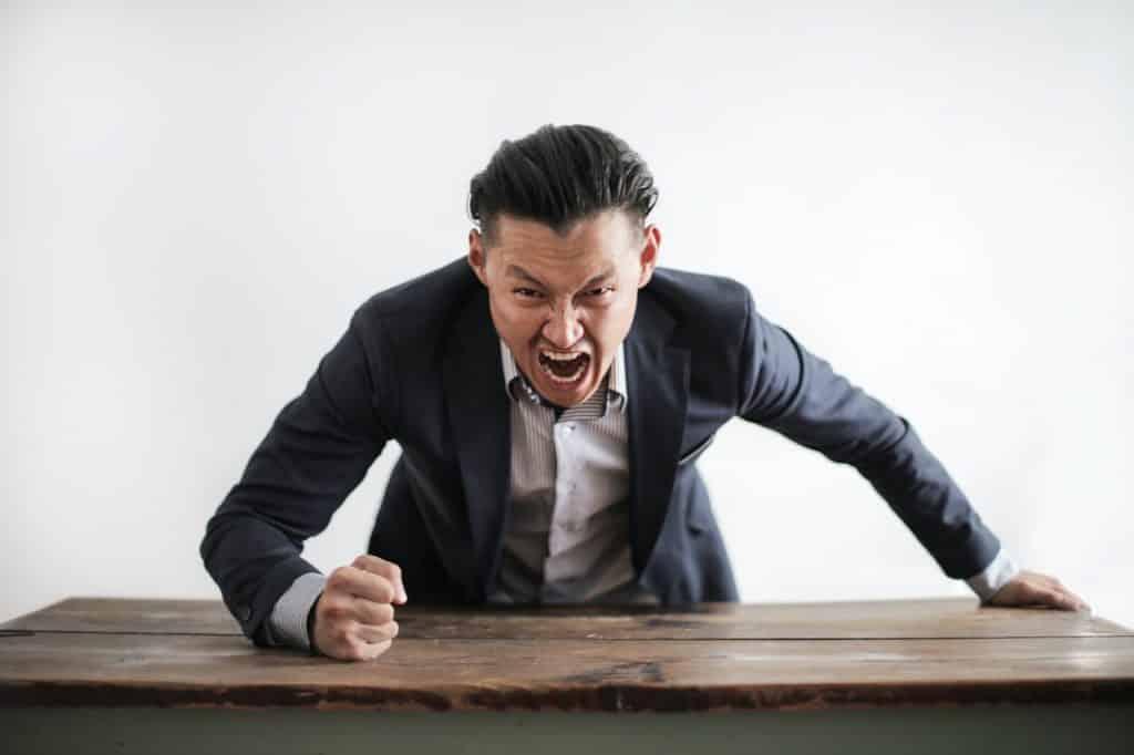 Homem com roupas sociais gritando enquanto bate com o punho na mesa de escritório.