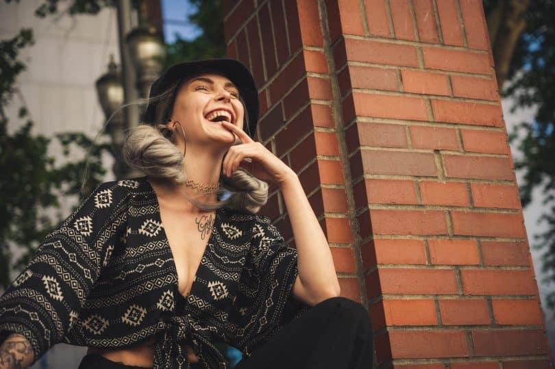 Mulher sorrindo de olhos fechados