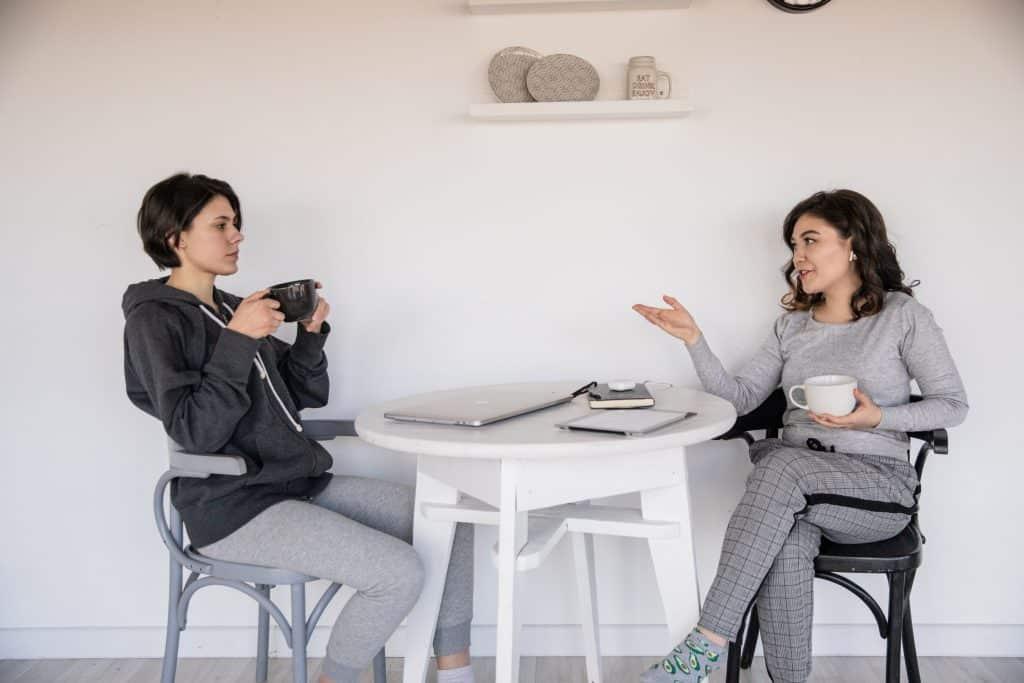 Mulheres sentadas em uma mesa segurando xícara de café