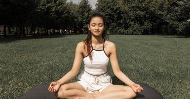 Mulher sentada em um gramado meditando
