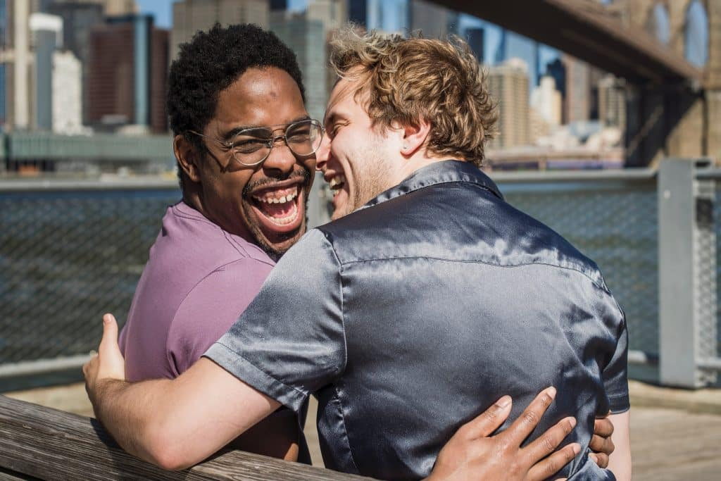 Dois homens sorrindo abraçados