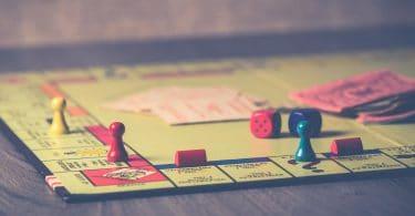 Foto de tabuleiro de jogo, verde, com peões coloridos, dados vermelhos e cartas, tudo em cima de uma mesa de madeira escura.
