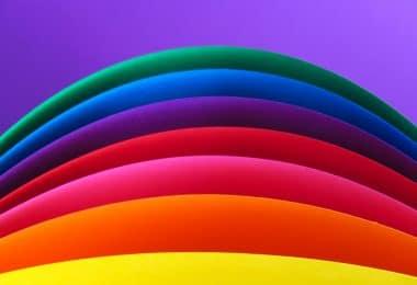 Ilustração gráfica de faixas coloridas, nas cores e sequência amarelo, laranja, rosa, vermelho, roxo, azul e verde, todas em cima de um fundo roxo.