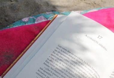 Livro aberto, com páginas brancas, colocado em cima de uma toalha rosa, no chão.