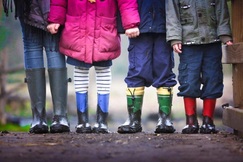 Foto de quatro crianças, três meninos e uma menina, só da cintura para baixo, todos vestindo roupas de frio coloridas e galochas de chuva.