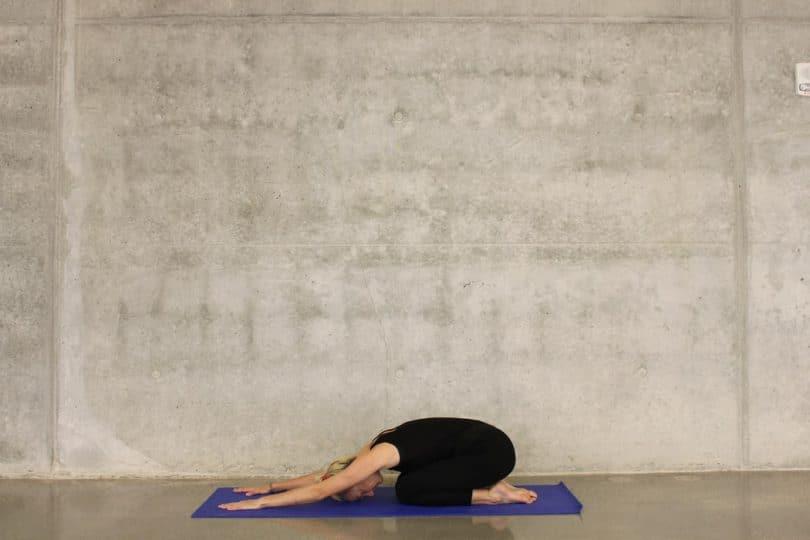 Mulher branca, vestindo roupas pretas, ajoelhada, tentando encostar o rosto no chão, em cima de um tapete de yoga roxo, colocado em um piso de cimento.