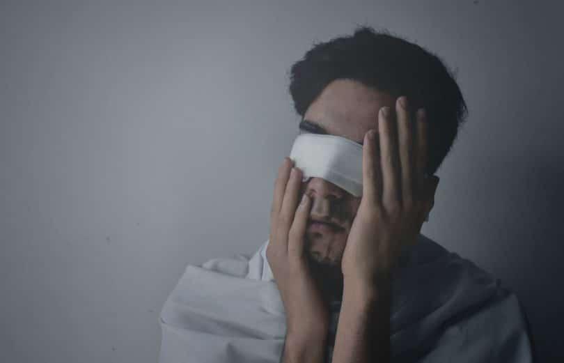 Homem jovem, vestindo camiseta branca, usando uma venda branca nos olhos, com as duas mãos tocando o rosto.