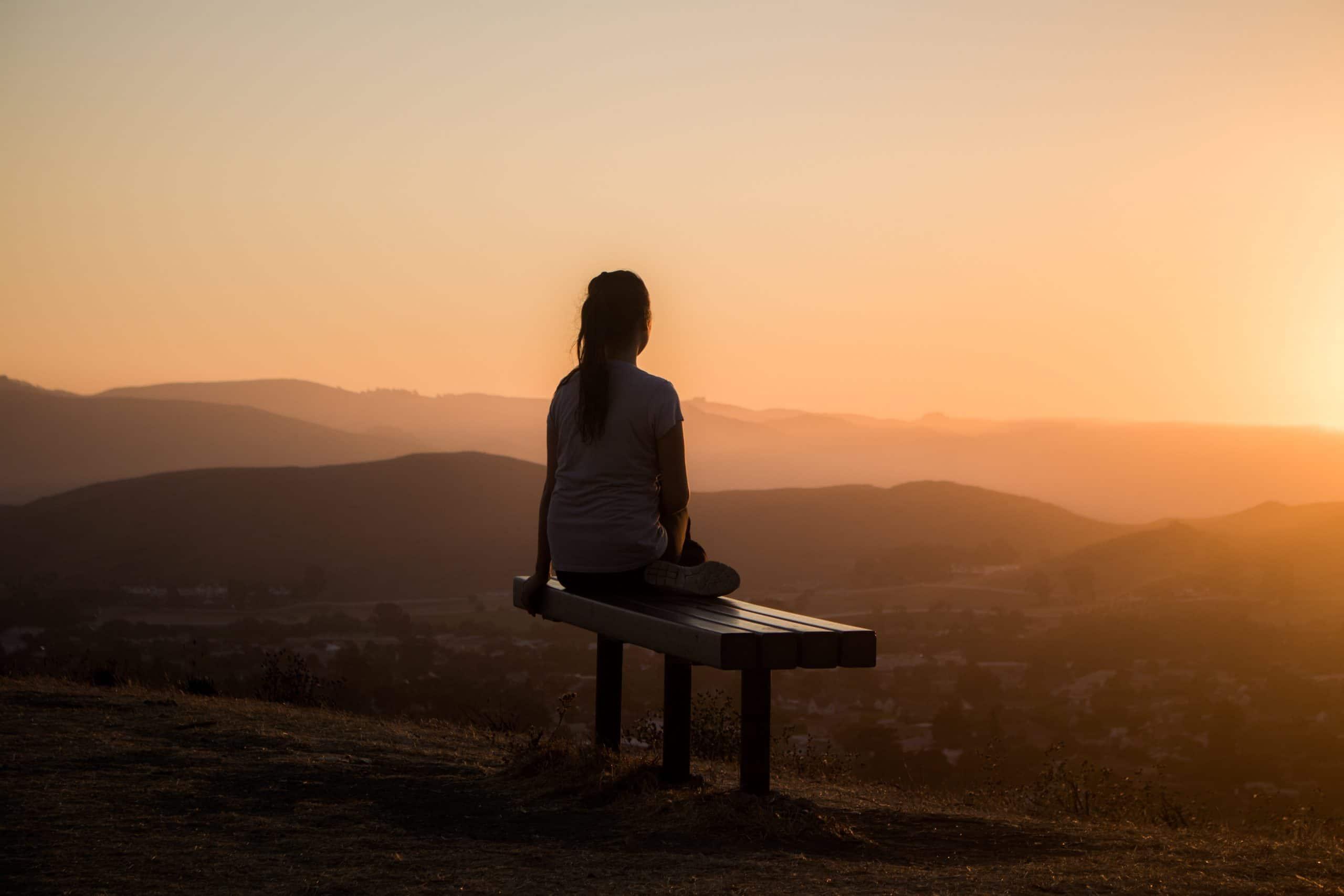 Mulher vista de costas sentada em um banco, ao por do sol, meditando.