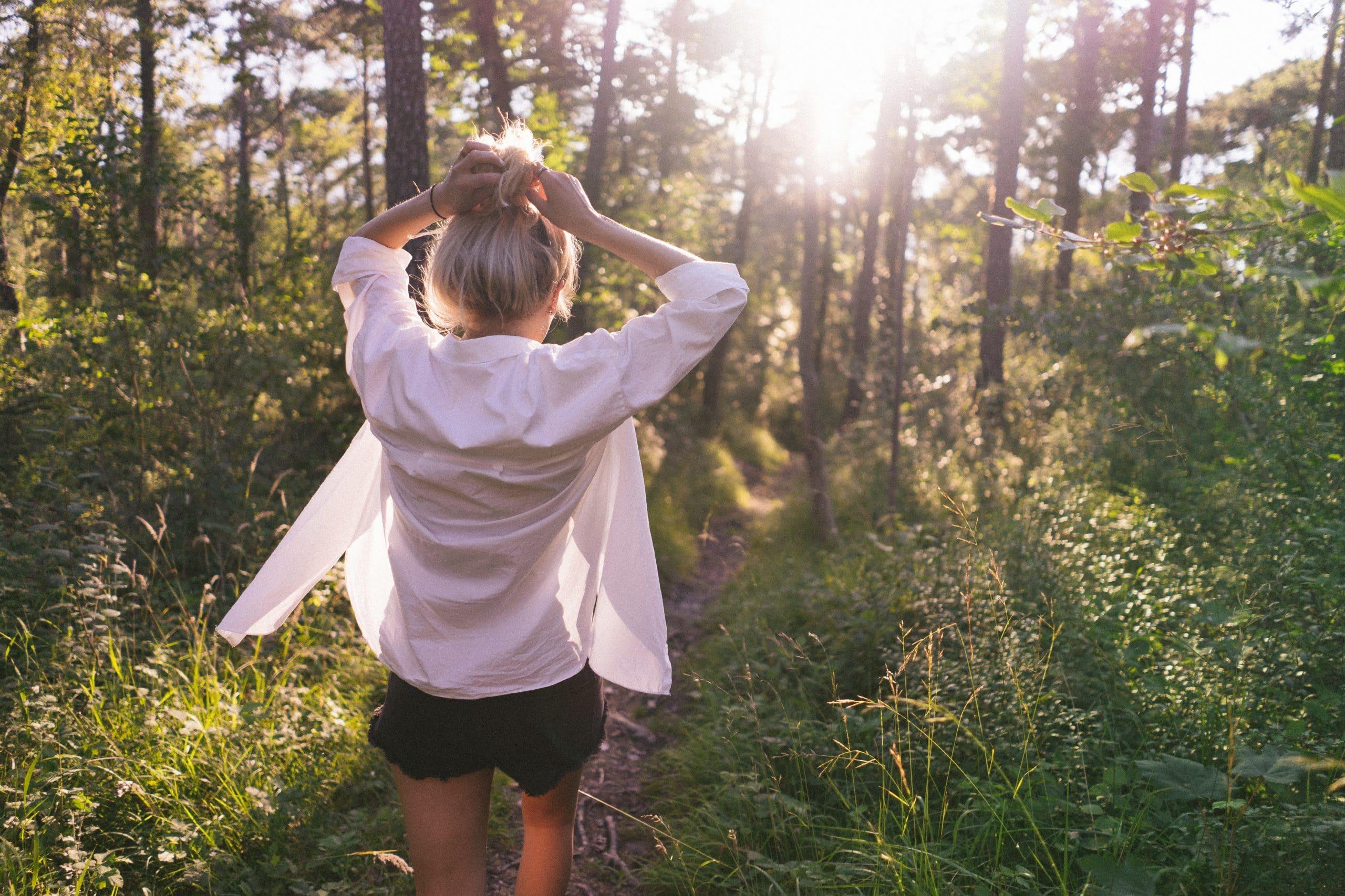 Mulher de costas caminhando em trilha