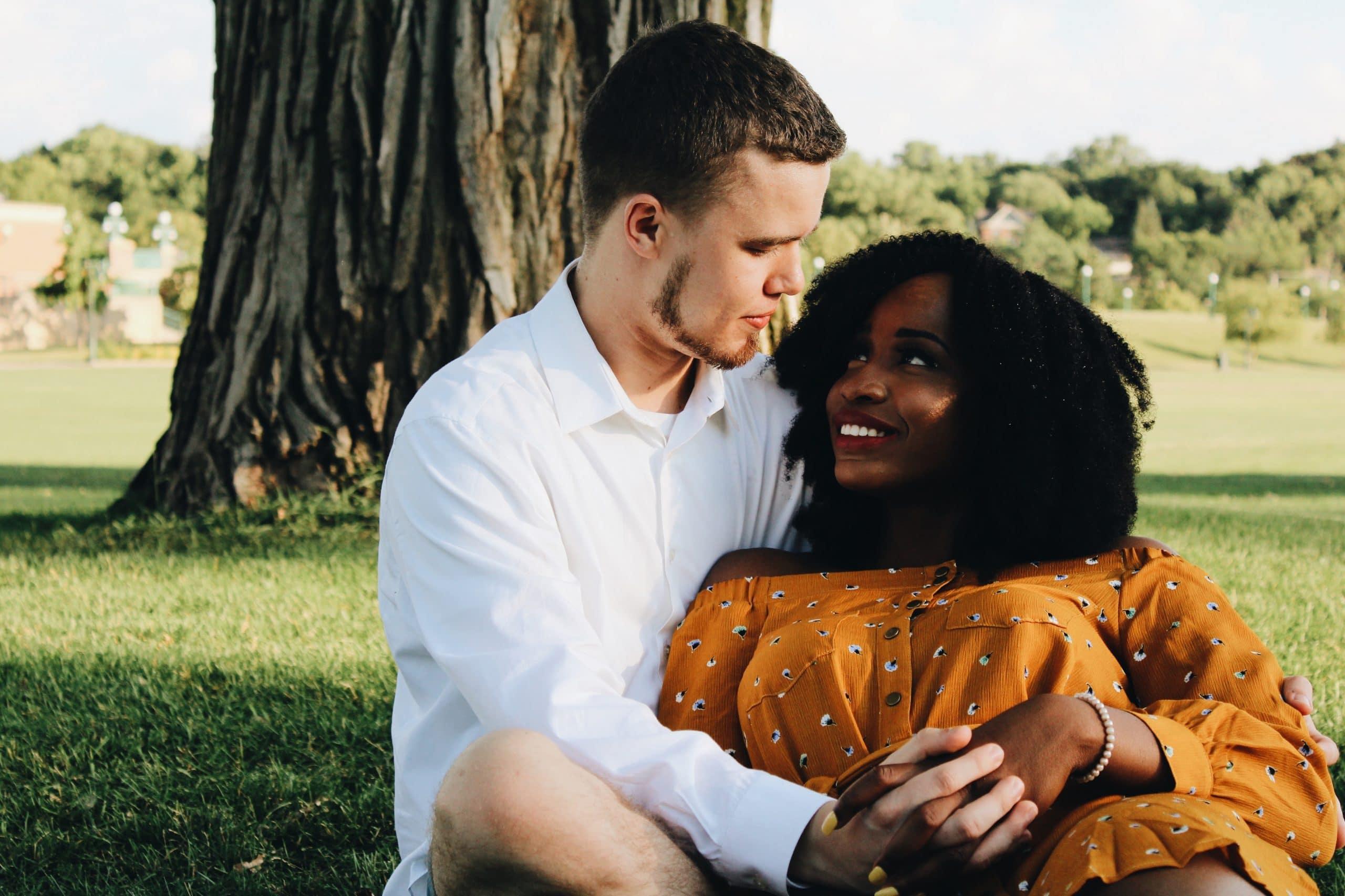 Casal sentado abraçado se olhando