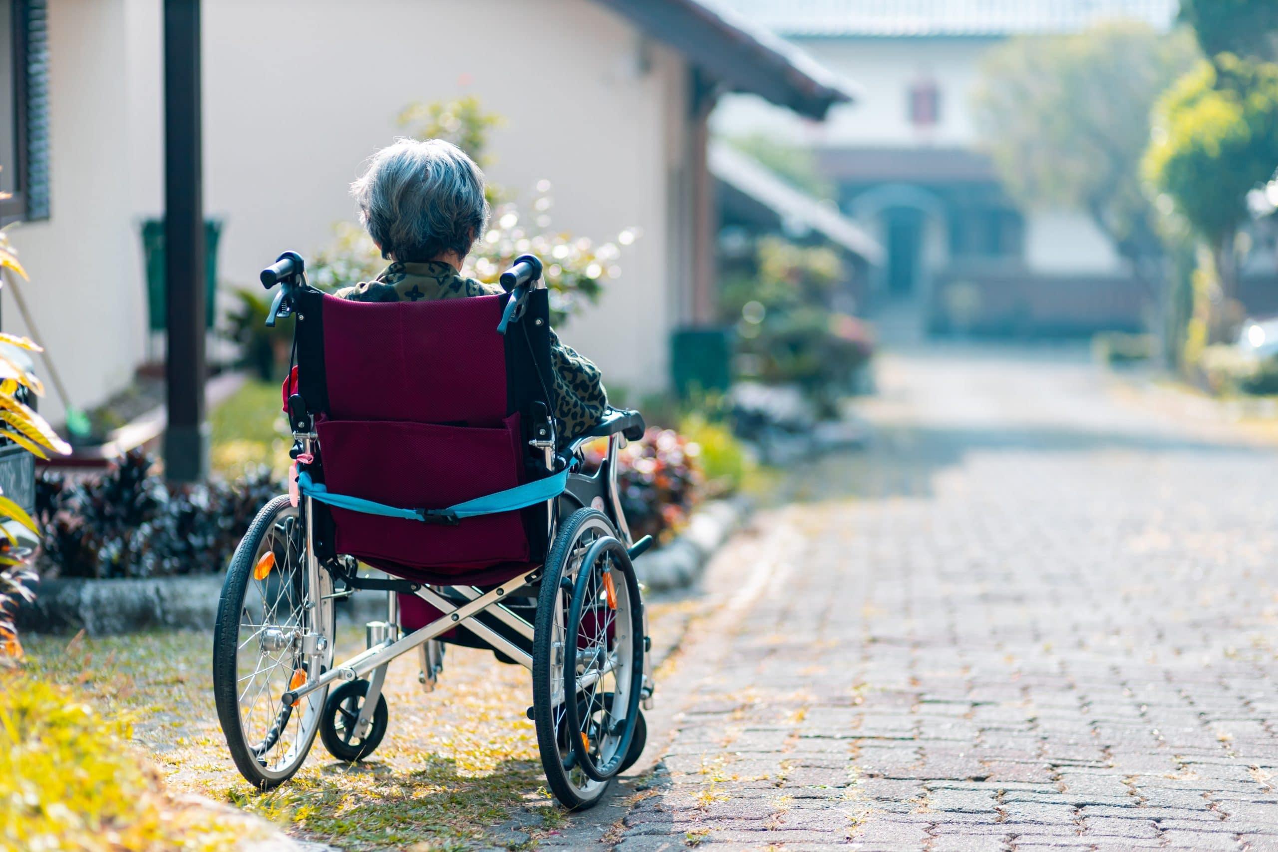 Mulher idosa cadeirante em um jardim.