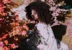 Mulher branca iluminada pelo Sol e sombra de folhas.