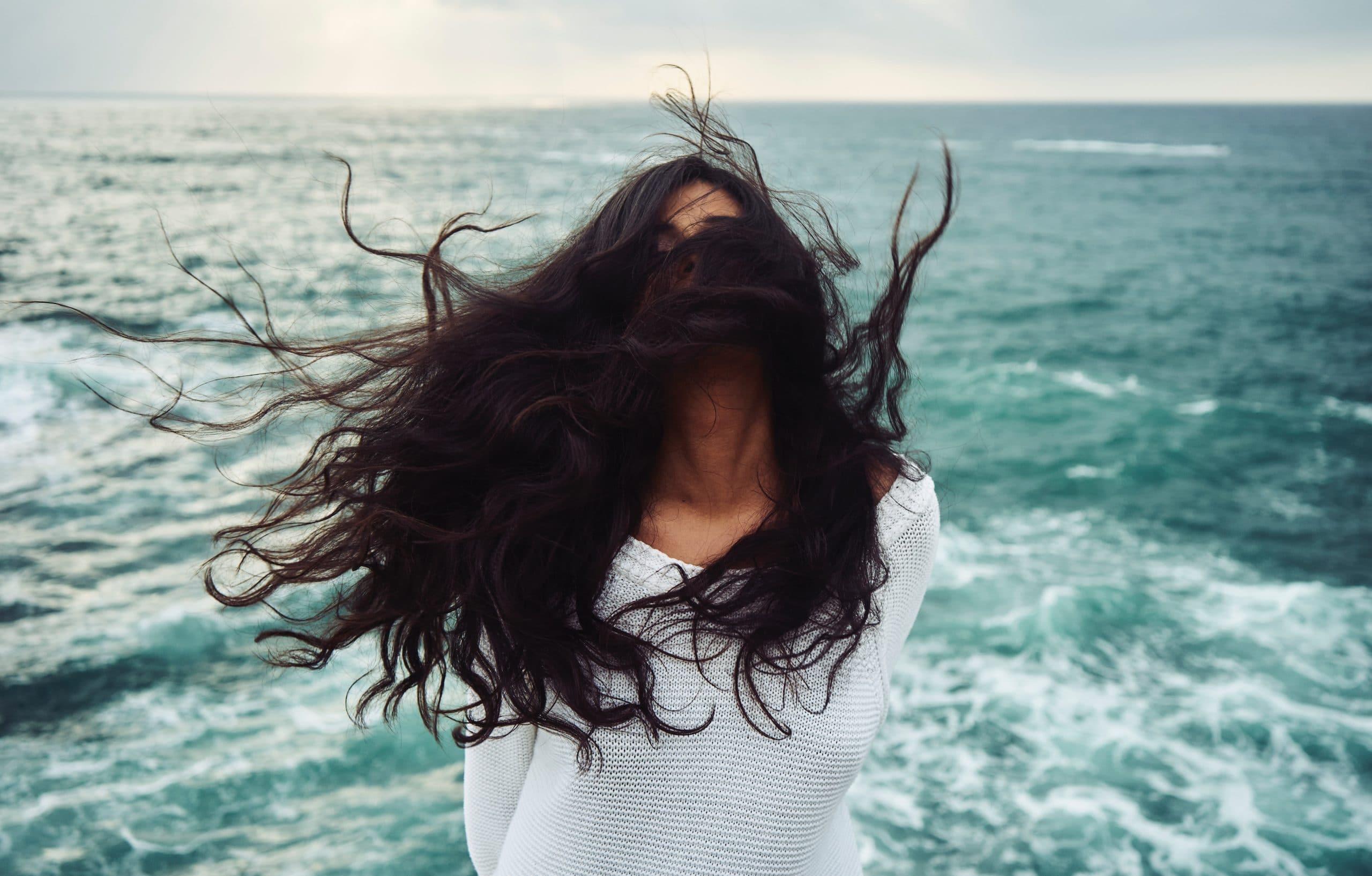 Mulher com os cabelos voando de frente para o mar.