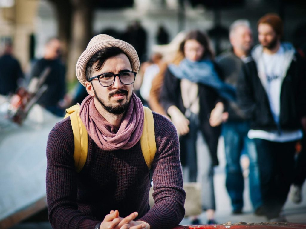 Homem com barba e bigode, usando cachecol lilás, óculos preto e um chapéu bege.  Está olhando para o infinito. Ao fundo outras pessoas compõem o cenário.