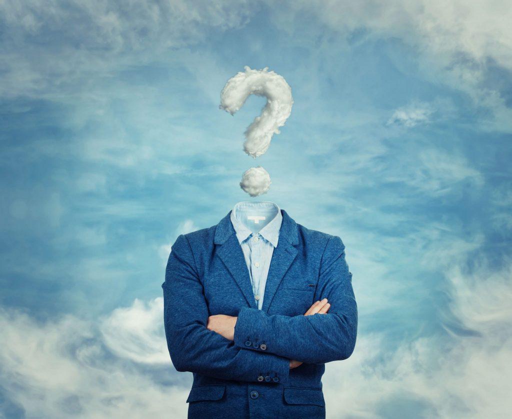 Ilustração gráfica de corpo de homem, vestindo um terno azul, com os braços cruzados. No lugar da cabeça há um grande ponto de interrogação, feito de nuvem. Ao fundo há um belo céu claro, cheio de nuvens.