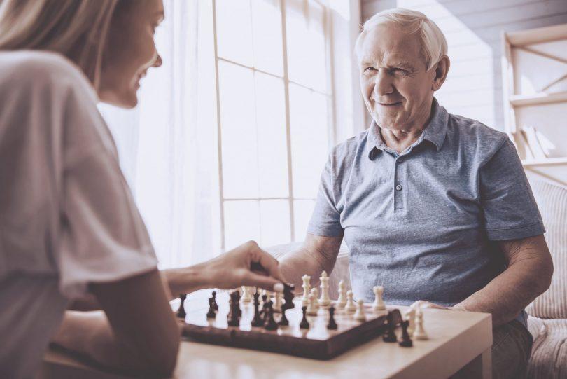 Mulher jovem jogando xadrez com senhor idoso. Ambos estão sorrindo.