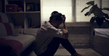 Mulher deprimida sentada no chão, com os joelhos flexionados e a cabeça apoiada na mão direita.