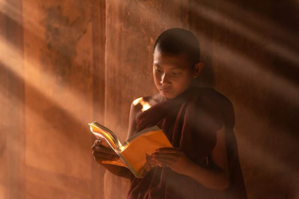 Jovem monge budista segurando sobre as suas mãos um livro aberto. Ele está de pé e sobre ele uma luz do sol.