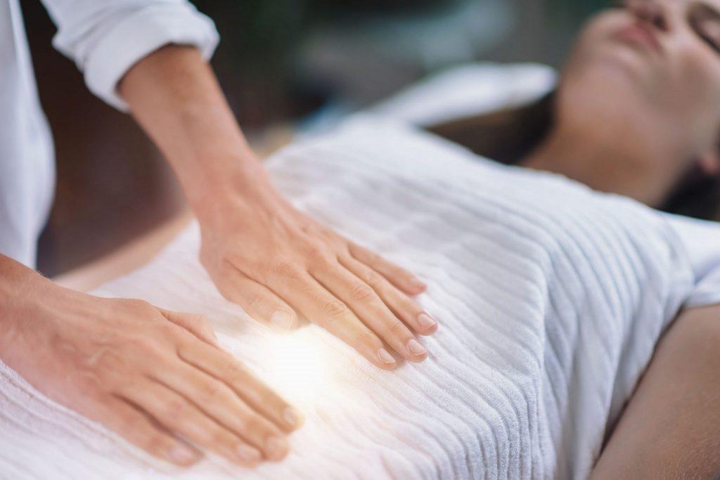 Pessoa praticando Reiki em mulher deitada. A terapeuta tem suas mãos sobre o abdômen e emanando luz de suas mãos.