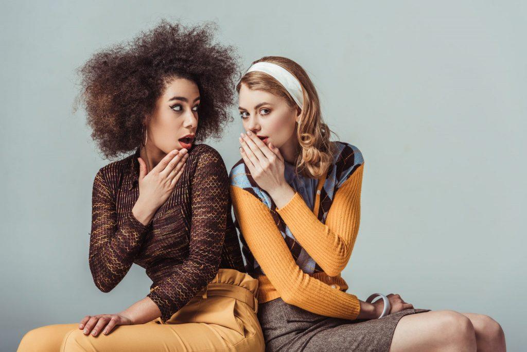 Duas mulheres, sendo uma negra e outra loura, fazendo estilo fofoca. Ambas estã sentadas lado a lado.