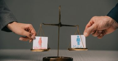 """Balança se equilibrando entre dois papeis com os escritos """"homens"""" e """"mulheres"""""""