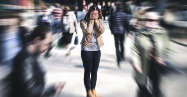 Mulher em pé no meio de uma multidão, cobrindo o rosto com as mãos enquanto têm um ataque de pânico.