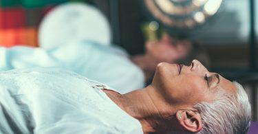 Mulher deitada de olhos fechados meditando