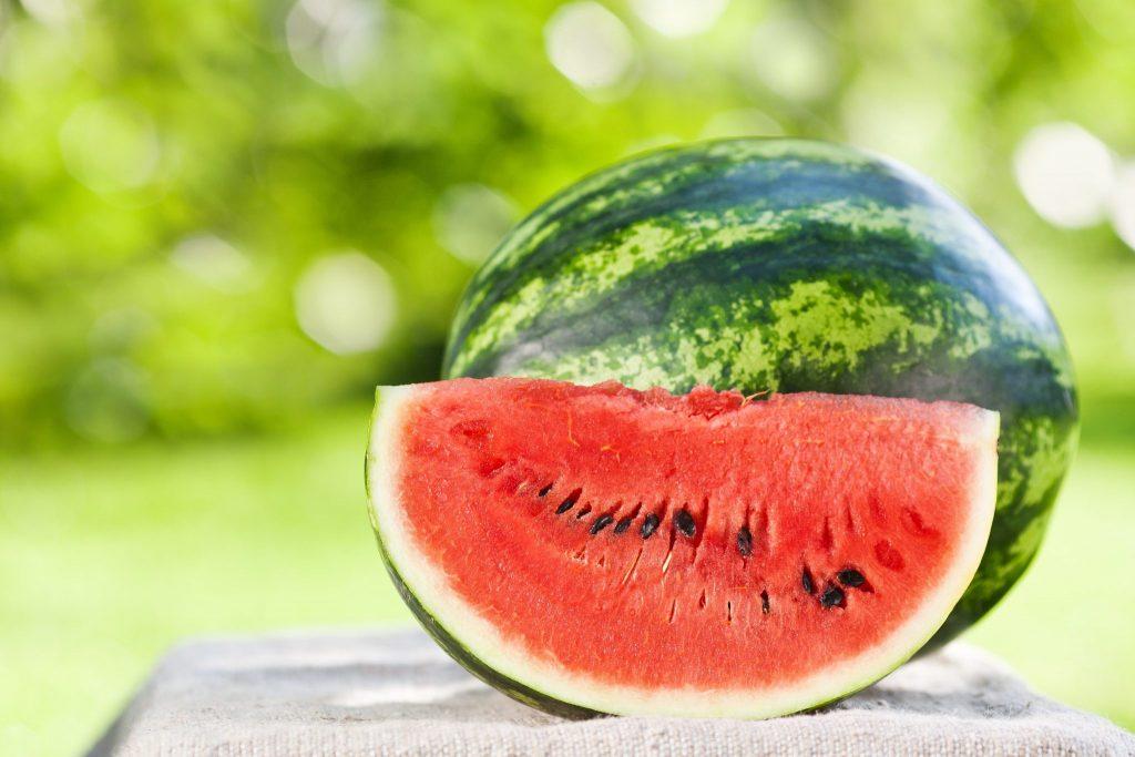 Melancia inteira sobre uma mesa e ao lado uma fatia da fruta já pronta para ser consumida. Ao fundo uma folhagem verde.