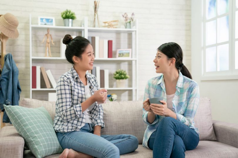 Duas mulheres sentadas no sofá conversando enquanto seguram xícaras com bebida.