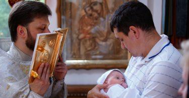 Homem segura bebê durante batizado, enquanto padre beija a bíblia.