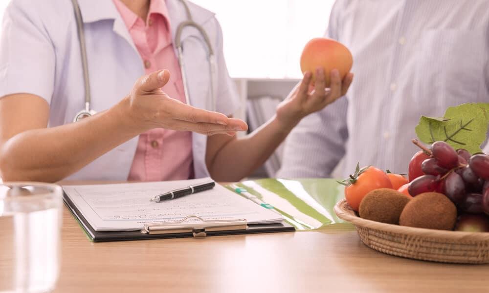 Imagem de uma médica com o seu paciente. Ela está expliando métodos de dieta. Ela segura uma fruta em suas mãos. Sobre a sua mesa encontra-se uma prancheta com anotações e uma fruteira com uvas, caquis e kiwis.
