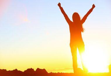 Silhueta de mulher de costas comemorando com sol refletindo