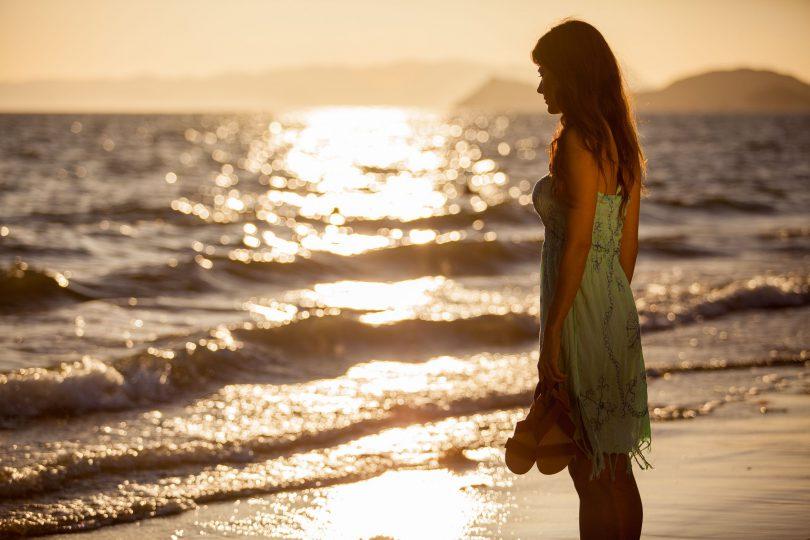Mulher na beira da praia com chinelos na mão