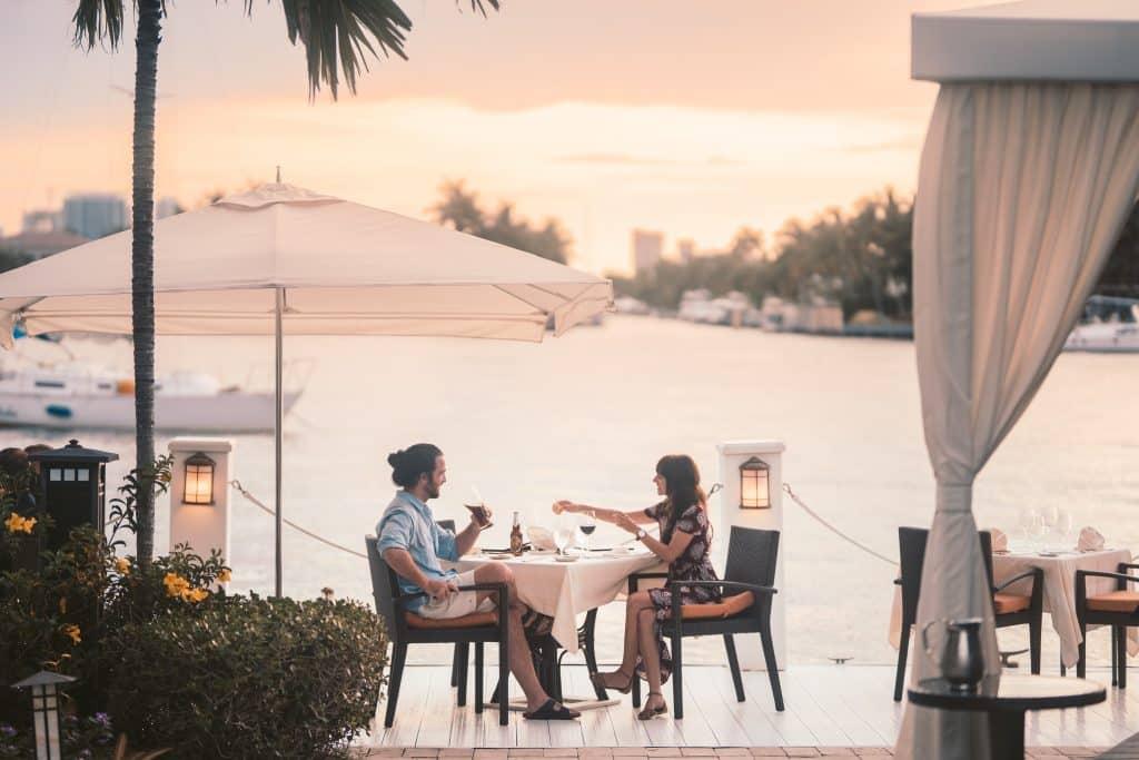 Homem e mulher sentados em um restaurante à beira mar, conversando,.