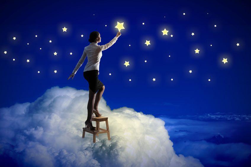 Imagem de uma mulher em pé em um banquinho, tentando pegar uma estrela, como se estivesse no céu.
