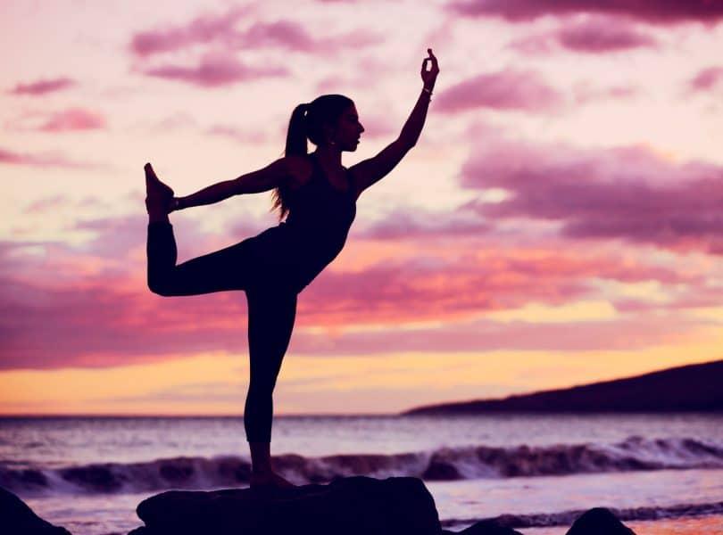Silhueta de mulher praticando yoga com o céu roxo ao fundo.