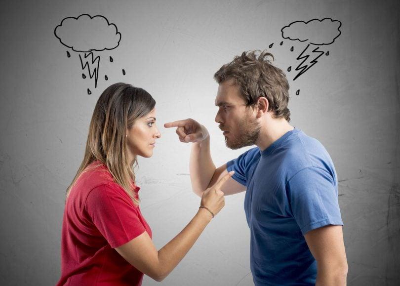 Casal de frente apontando o dedo um para o outro
