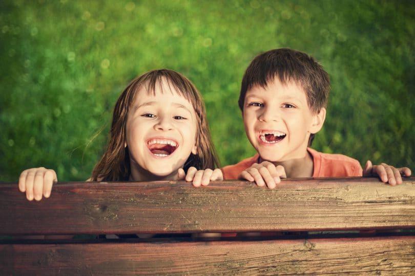 Retrato ao ar livre da menina sorridente e menino que perdeu os dentes de leite