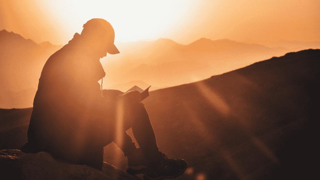 Silhueta de homem olhando o por do sol na montanha