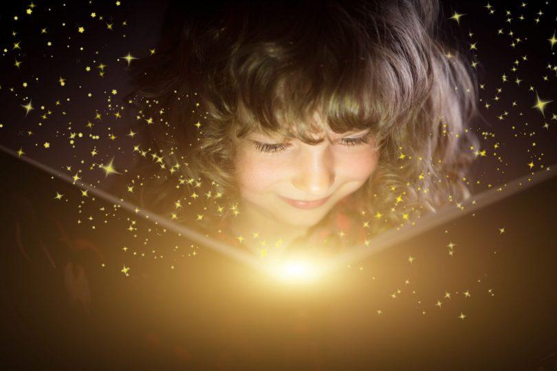 Criança lendo livro saindo luzes mágicas