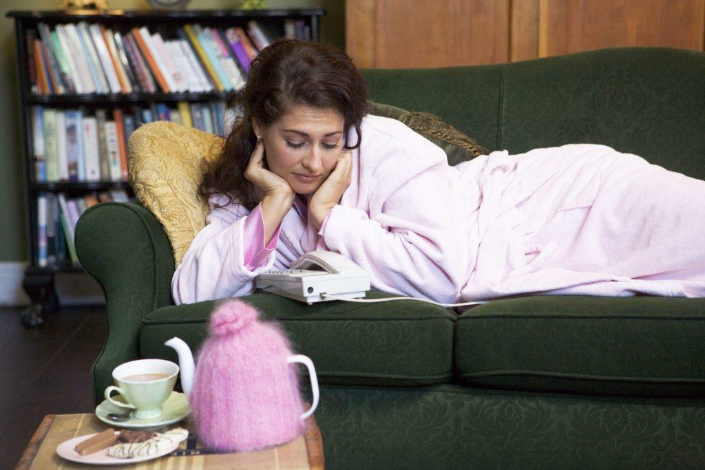 Mulher ansiosa deitada no sofá e olhando para o telefone esperando ele tocar. Ela está de roupão rosa.