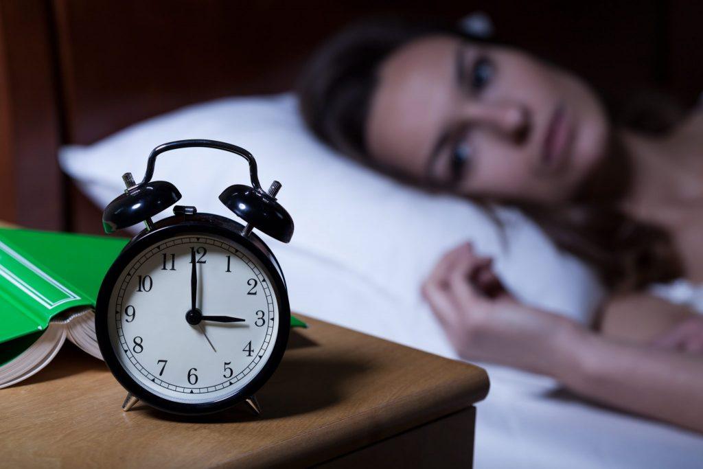 Mulher deitada na cama. Ela está acordada e olhando para o despertador que está ao lado dela sobre um criado mudo. Ela está ansiosa e não consegue dormir. O relógio marca três da manhã.