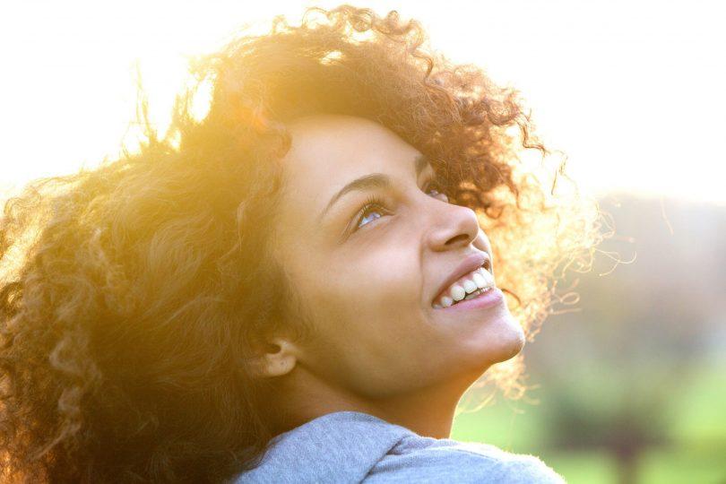 Mulher sorrindo olhando para cima.