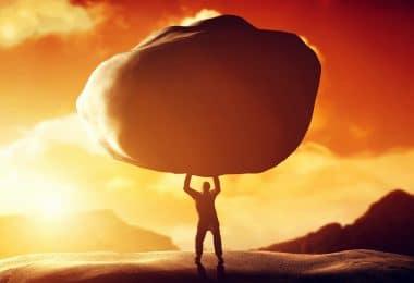 Silhueta de pessoa forte segurando uma pedra enorme sobre a sua cabeça. Ao fundo o céu laranja graças ao pôr do sol.