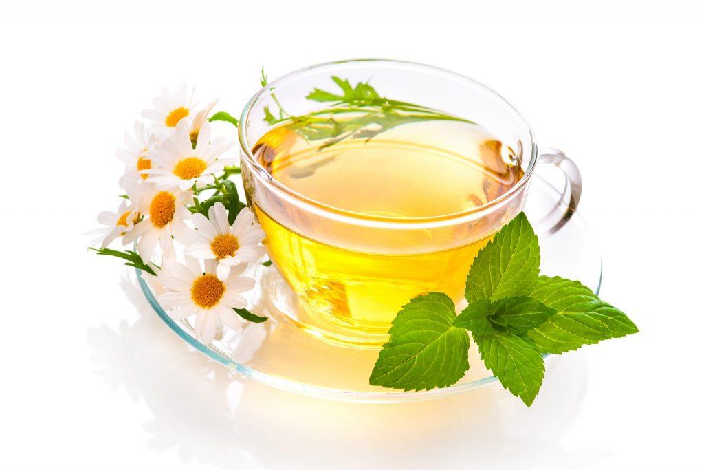 Xícara de vidro com chá de camomila. A xícara está sobre um pires também de vidro, decorado com margaridas e hortelã.